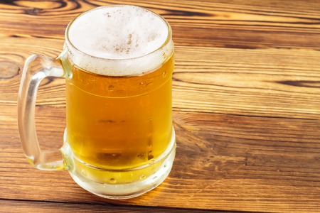 bleb: Mug of cold beer on wooden table, close-up view