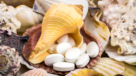 food supplement: Calcium natural food supplement pills on the beautiful, mixed seashells background