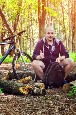 cycler: Cyclist with backpack, smiling young man shows thumb up, in beautiful forest, summertime journey Stock Photo