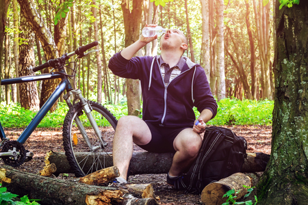 cycler: Cyclist with backpack, young man drinking water from bottle, in beautiful forest, summertime journey