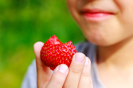 displeasure: Girl bit off piece of strawberry and grimaced, displeasure emotion, focus on the berry Stock Photo