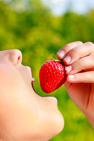 puts: Child puts juicy ripe strawberries in the mouth close-up view