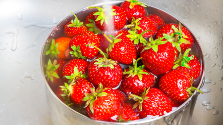 bowl sink: Bowl of organic strawberry in the sink under running water.