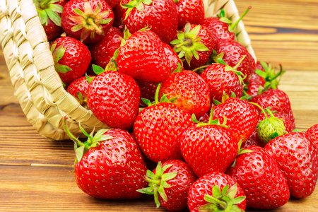poured: Full basket of ripe strawberries that are poured out on the wooden table Stock Photo