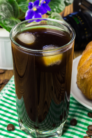 Glassful of black coffee with ice on green napkin. croissant, vintage camera, flowerpot, wooden table, selective focus.