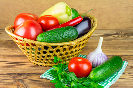 Group of backyard vegetables, tomato, cucumber, peppers, garlic, eggplant in wicker basket on wooden background Stock Photo