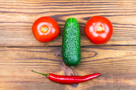 chilli pepper: Backyard vegetables, tomatoes, cucumber and chilli pepper in the shape of head on wooden background. Stock Photo