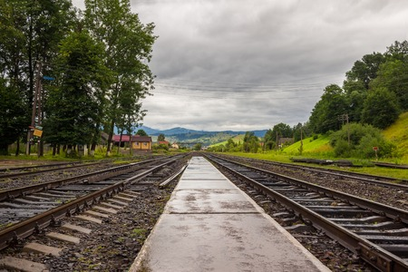 Railroad near the mountains at the cloudy day. Stock Photo
