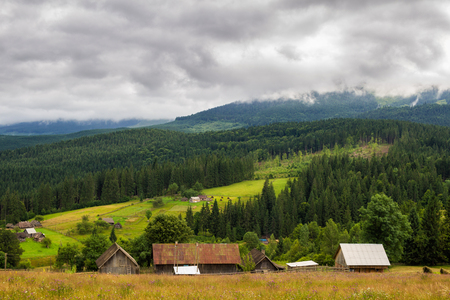 Rural houses in Carpathian mountains. Cloudy summer landscape, Ukraine, Europe Reklamní fotografie