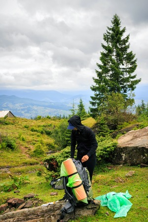stopped: Girl with backpack stopped to the rest in Carpathian mountains, summertime journey, travel concept Stock Photo