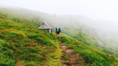 Tourist goes along mountain trail to the small wooden house on hill of ridge in mist, Carpathians, Ukraine
