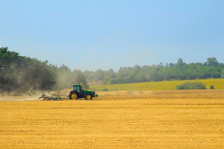 arando: Green tractor with harrow working on the yellow field in autumn
