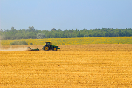 Green tractor with harrow working on the yellow field in autumn