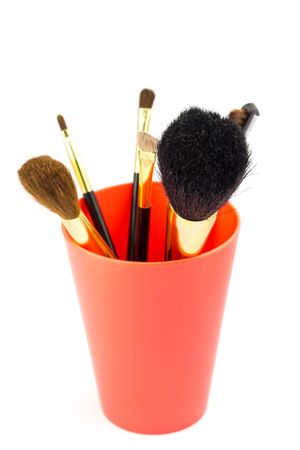 basic care: Professional cosmetic brushes for makeup in red holder isolated on white background Stock Photo