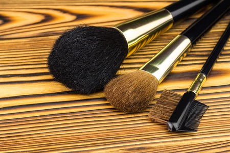 grooming product: Professional cosmetic brushes for makeup on wooden background Stock Photo