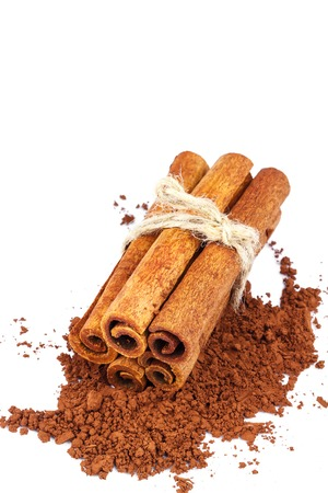 Group of cinnamon sticks on cacao powder, isolated on white background, close-up Stock Photo