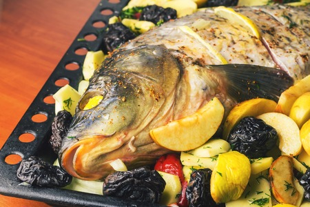 Carp fish prepared for cooking in baking dish with vegetables