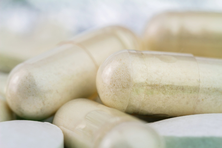 Natural food supplement pills, glucosamine capsules and calcium, macro image, soft blurred background
