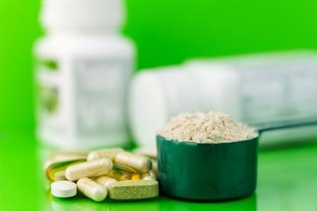 Mixed natuurlijk voedingssupplement pillen en proteïne poeder in plastic lepel op groene achtergrond