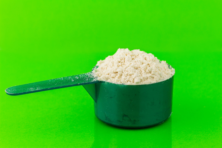 plastic scoop: Protein powder in plastic spoon on green background