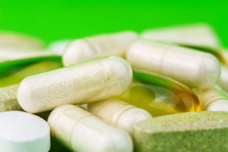 Mixed natural food supplement pills, omega 3, calcium, multivitamin and glucosamine capsules on green background