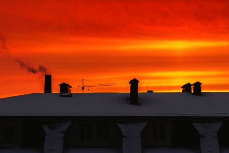 Red, orange, vivid sky at sunrise over the building in the city Stock Photo
