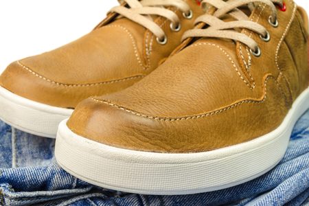 close-up view of tan color, leather sneakers on jeans pant