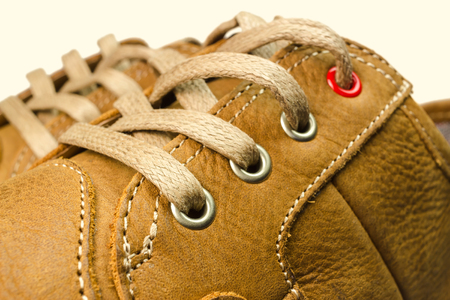 close-up view of lacing on tan color, leather sneakers isolated on white background Stock Photo