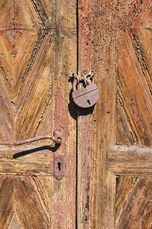 Locked old wooden door with cracks and rusty lock, close-up view Stock Photo