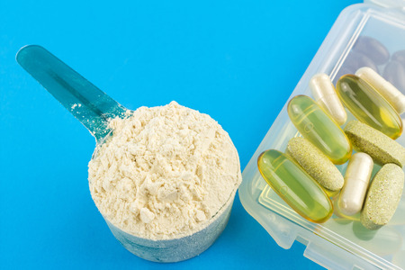 plastic scoop: Protein powder in measuring plastic spoon and vitamin complex, omega 3, glucosamine capsules, supplements on blue background, sports nutrition.
