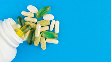 Vitamin complex, omega 3, glucosamine capsules, multivitamin supplements and white container on blue background, top view.