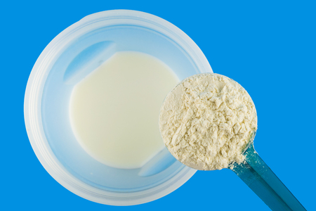 Full measuring spoon with protein powder, directly above at shaker bottle with milk on blue background, sports nutrition, top view.