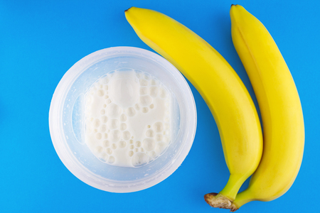 bubble acid: Cooked milk protein cocktail in the shaker bottle and two banana on blue background, sports nutrition after training, top view.
