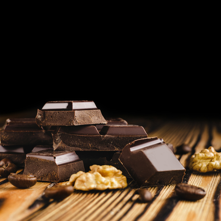 Pieces of bitter, dark chocolate, cubes on heap, walnut core and coffee bean on wooden background, close-up view. Stock Photo