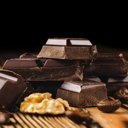 苦い、ダーク チョコレートの部分は木製の背景、クローズ アップ ビューでコーヒー豆、クルミ コア ヒープ上のキューブ。
