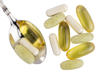 Vitamin complex, omega 3, glucosamine capsules, multivitamin supplements in the spoon isolated on white background, top view.