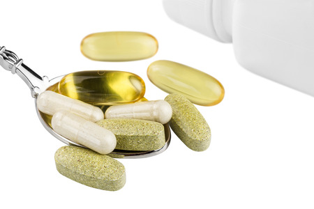 Vitamin complex, omega 3, glucosamine capsules, multivitamin supplements in the spoon and white container isolated on white background.