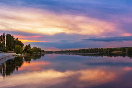 Vivid scenery of sunset at the river, colorful, dramatic evening sky reflected in the water, hdr image. Khmelnytskyi, Ukraine. Stock Photo