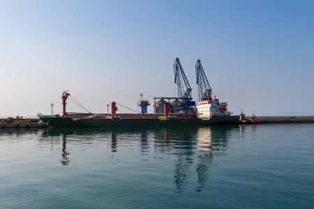 Big cargo ship in sea port terminal with cranes in Balchik, Bulgaria.