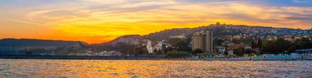 Panorama of golden sunset scenery on Black sea coast, view on Balchik city on Bulgaria.