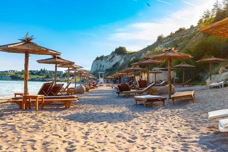 Black sea coast, sand beach with sunbeds and straw umbrellas, summer sea rest concept. Stock Photo