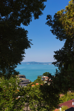 balchik: View sea through foliage from altitude in Balchik town, black sea coast in Bulgaria. Stock Photo