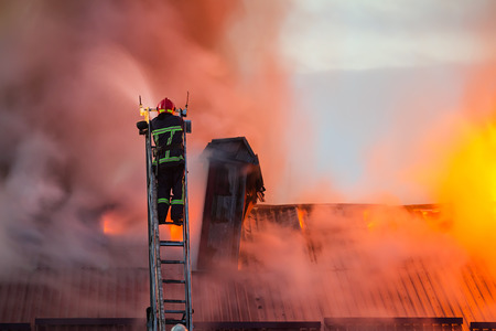 Firefighter or fireman on the ladder extinguishes burning fire flame with smoke on the apartment house roof.
