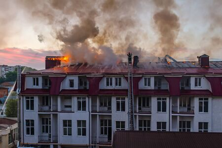 heat loss: Burning fire flame with smoke on the apartment house roof in the city, firefighter on the ladder extinguishes fire.
