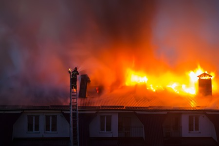 heat loss: Burning fire flame with smoke on the apartment house roof in the city, firefighter or fireman on the ladder extinguishes fire.