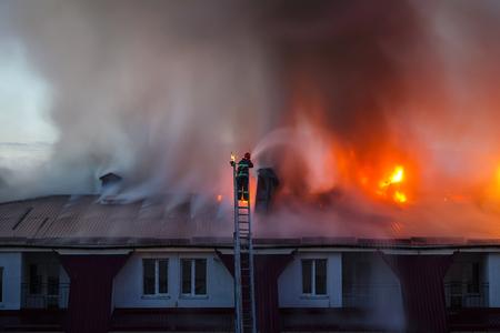 Brandende vuurvlam met rook op het dak van het appartementshuis in de stad, brandweerman of brandweerman op de ladder blust vuur.
