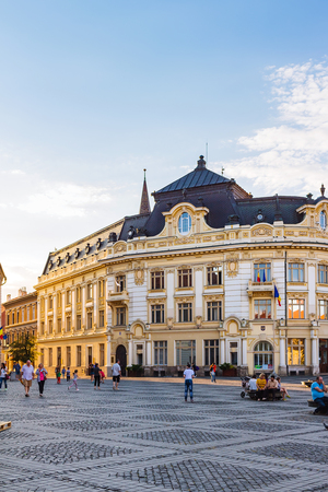 SIBIU, ROMANIA - JUNE 19, 2017: Large, main square Huet with City Hall and tourists on the street, ancient, medieval city.