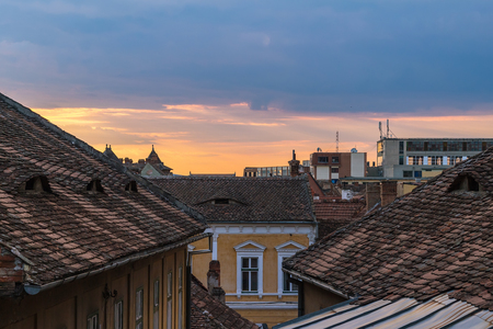 Architectural details and house roofs with attic windows designed in eyes shape in Sibiu city at sunset time, Romania.