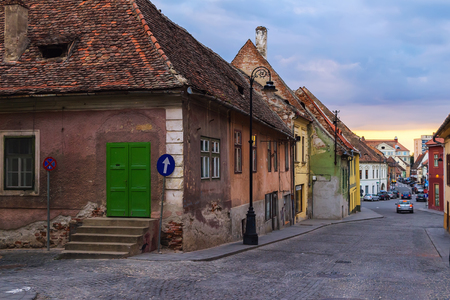 View on the medieval street with ancient houses at sunset time in the Sibiu city, Romania.
