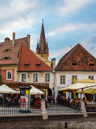 SIBIU, ROMANIA - JUNE 19, 2017: View on the Lutheran Cathedral tower in the street with medieval houses and outdoors cafe with people.